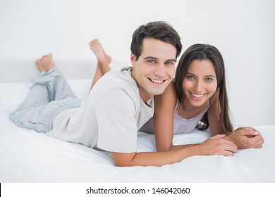 Young couple lying together in bed in the bedroom