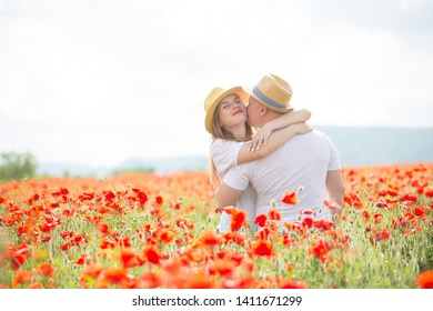 A young couple made a date in a beautiful field of red poppies. Romantic walk in the village
