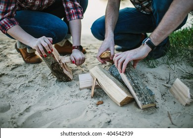 Young couple make fireplace on the beach. Shallow focus.