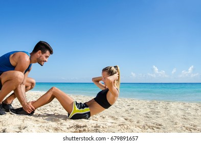 Young couple making ab crunch at the beach