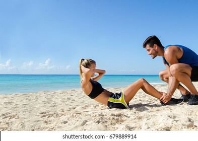 Young couple making abs crunch at the beach