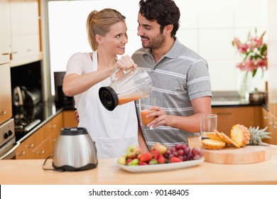 Young couple making fresh fruits juice in their kitchen