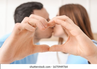 Young couple making heart shape with their hands, closeup