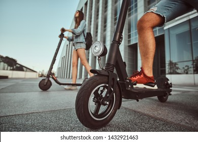 Young couple are making interesting composition from their scooters while posing for photographer.