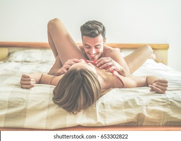 Young couple making passionate foreplay before sex in hotel room - Handsome lovers having sexual romantic moments - Relationship under the cover concept - Focus on man hands - Warm contrast filter