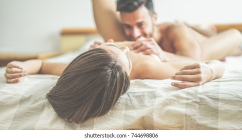 Young couple making passionate foreplay before sex in hotel room - Handsome lovers having sexual romantic moments under the cover -  Sexual concept - Focus on right woman hand - Warm contrast filter