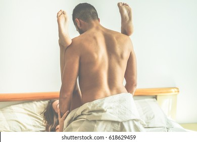 Young couple making passionate sex in hotel room - Handsome lovers having sexual romantic moments - Relationship under the cover concept - Focus on man's ear - Warm contrast filter