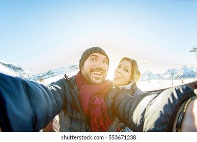 Young couple making selfie snow resort mountain background with mobile phone - Tourist laughing and making funny emotional faces in smartphone camera - Vacation concept - Focus on him - Warm filter
