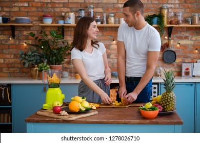 Young couple making smoothie in kitchen