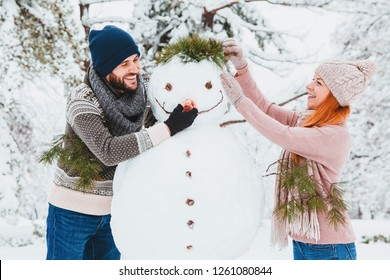 Young couple making snowman in the park