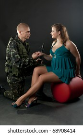 Young couple, male model dressed in military and female model dressed in civilian, pose in studio