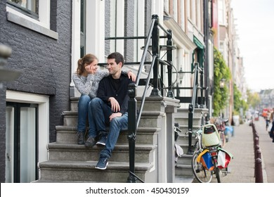 young couple, man and woman in Amsterdam, Netherlands, sitting on steps in front of holland house, talking