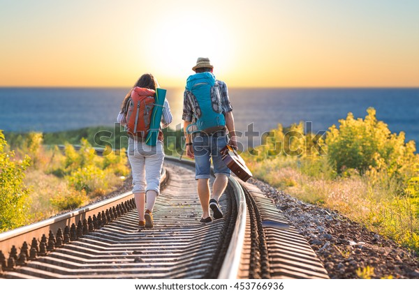 Young Couple Man and Woman with Backpacks and Guitar in casual Travel Clothes walking along Railroad toward Sea Beach Sunrise on Horizon