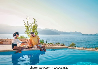 young couple man and woman by the pool having breakfast during vacation