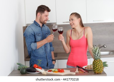 Young couple, man and woman celebrating the new modern kitchen. Beautiful girl and likeable boy with a glass of red wine.