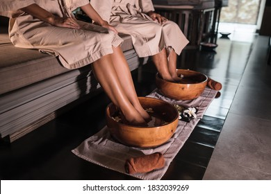 Young couple man and woman dipping their feet in a bowl, waiting for the spa staff to cleanse. Feet in a bowl of floral scented water at the spa center.