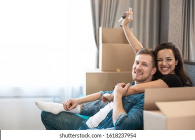 young couple man and woman looking excited having break on the sofa during moving to new appartment unpacking boxes, , moving process