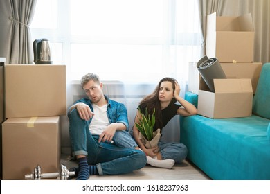 young couple man and woman looking tired sitting on the floor during moving to new appartment unpacking boxes, , moving process