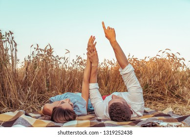 A young couple, man and woman meet sunset and dawn in summer in a wheat field. Lie on bedspread on ground. Concept of love caring, hugging family happiness and support. Hands show the stars.