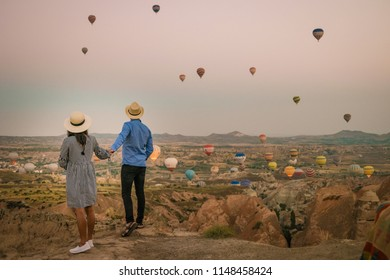 young couple man and woman sitting on the rocks watching sunrise, Goreme Capadocia kapadoya Turkey, Sunrise over the hills with hot air balloons in the sky , colorful landscape