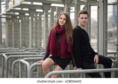 Young couple man and woman sitting on the railing
