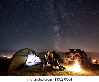 Young couple man and woman trevelers sitting near glowing tourist tent, burning campfire, atv quad motorbike on the top of mountain, enjoying beautiful view of night sky full of stars and Milky way