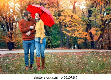 Young couple man and woman walk under an umbrella in wet rainy weather, walk October lovers