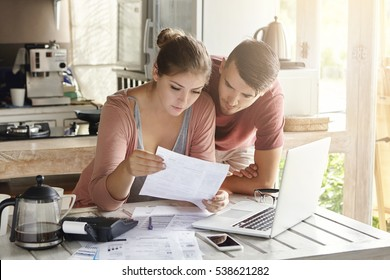 Young couple managing finances, reviewing their bank accounts using laptop computer and calculator at modern kitchen. Woman and man doing paperwork together, paying taxes online on notebook pc