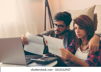 Young couple managing their finances, reviewing their bank accounts and paying the bills using laptop computer. Focus on the man