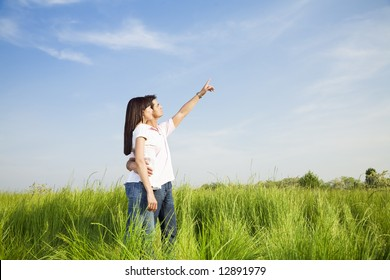 young couple in meadow with hand in air, hugging. Copy space