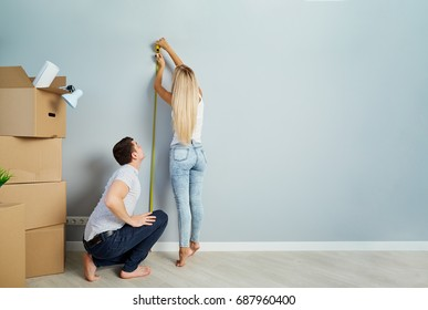 A young couple measures a tape measure on a wall in a new apartm
