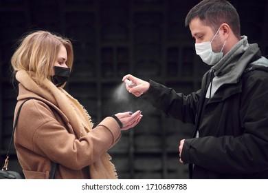 Junge Paare in medizinischen Masken mit antiseptischer Coronavirus-Epidemie