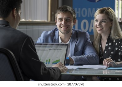 A young couple meeting with a banker for a home loan
