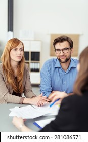 Young couple meeting with a broker or agent sitting at her desk in the office listening to te presentation with attentive expressions