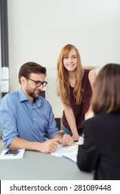 Young couple in a meeting with a broker or agent sitting at her desk looking at paperwork with focus to the smiling wife