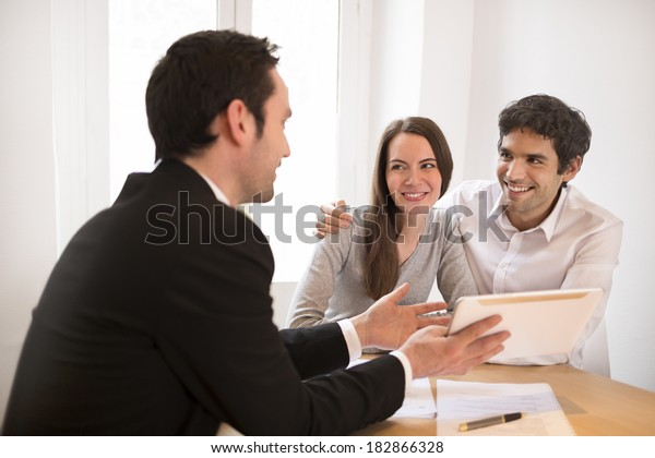Young Couple meeting real-estate agent to buy property, presentation on the tablet pc