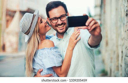 Young couple at the meeting. Romantic couple taking a selfie with smart phone. Love, dating, romance