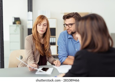 Young couple meeting with their investment broker discussing a document with her during the presentation, view over the agents shoulder