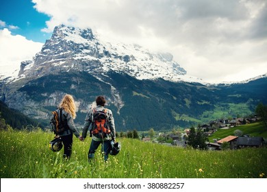 Young couple of motorcycle travelers enjoying a valley view in the summer mountains of Switzerland, Grindelwald. Moto tourism and moto travellers lifestyle while traveling Europe