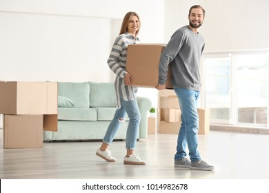 Young couple with moving box in room at new home