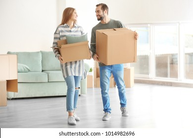 Young couple with moving boxes in room at new home