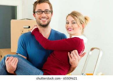 Young couple moving in a home or apartment, the man in carrying his woman