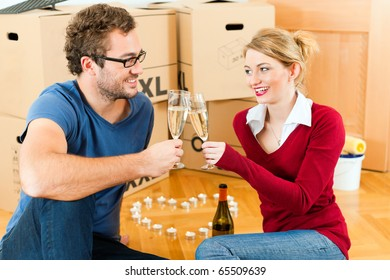 Young couple moving in a home or apartment, they are sitting on the wood floor drinking champagne having a break from renovation