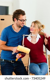 Young couple moving in a home or apartment, they are painting and doing renovation work
