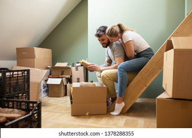 Young couple moving into new home.They find all memory book in the cardboard.