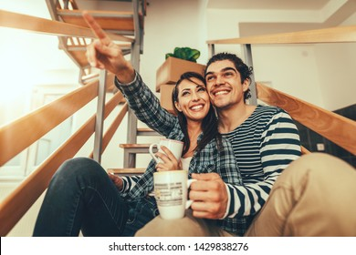 The young couple is moving into a new house. They are sitting on stairs and resting after bringing boxes with things to their new home.