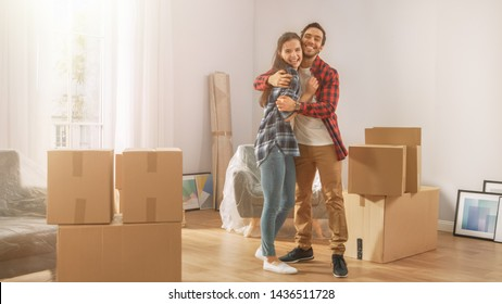 Young Couple Moving Into New Apartment, Carrying Cardboard Boxes with Stuff, Having Fun and Hugging. Boyfriend and Girlfriend Start Living Together, Unpacking Stuff. Room Lit by Warm Yellow Sunlight
