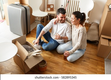 Young couple moving in new apartment.Sitting on floor and relaxing after cleaning and unpacking.