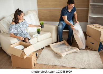 Young couple Moving in new home and unpacking carboard boxes.Almost done moving in.
