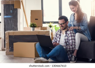 Young couple moving in new home. Sitting and relaxing after unpacking. Searching home decorating ideas on laptop. Online shopping.